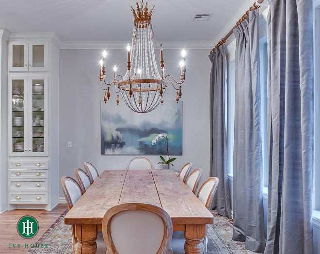 "Dining room. The dining room is set in front of wall to wall windows. The natural light brings in beautiful light to the space and also creates balance between the dark window treatments and the soft palette of the dining set. The chandelier is from Cyan Design ""Alexandra Chandelier"". The curtains are Dupioni Silk Drapes from Pottery Barn in Platinum Gray. The table was previously owned by the client and the Louis style chairs are made by Zentique (can be purchased through Wayfair). The art resembles the outdoors and adds a pop of color to the space. #diningroom Ivy House Interiors"