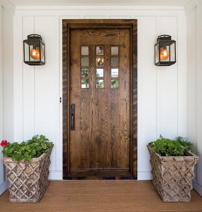 Farmhouse front door. White board and batten farmhouse exterior with wood front door. Farmhouse front door. Farmhouse wooden front door #Farmhouse #frontdoor #wooddoor #woodendoor #boardandbatten #homeexterior #entry J Taylor Designs