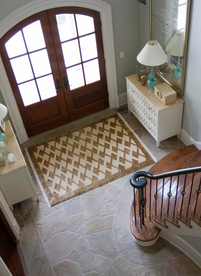 This foyer is tailored but welcoming at the same time. Using two consoles create a balanced symmetry in the space. Stair Risers and Baseboard Paint Color: Sherwin Williams Divine White. Handrail and Spindles: Benjamin Moore Black. Rug: Stark Tibetan Silk. Home Bunch Beautiful Homes of Instagram bluegraygal