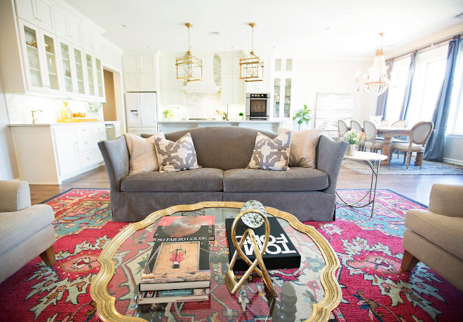Grey sofa. This updated living space has a more colorful rug from Wayfair. The designer kept the two arm chairs in cream, but changed the old beige couch for a gray couch. The right side of the room features a sideboard from Gabby Home, that can be purchased through Ivy House. The art above was found at an estate sale and is the same art featured in the Master Bath. The ginger jars boxes and other accessories can also be purchased through Ivy House. The small accent table between the chairs is also from Gabby Home and can be purchased through Ivy House. grey-sofa #Greysofa #sofa Ivy House Interiors