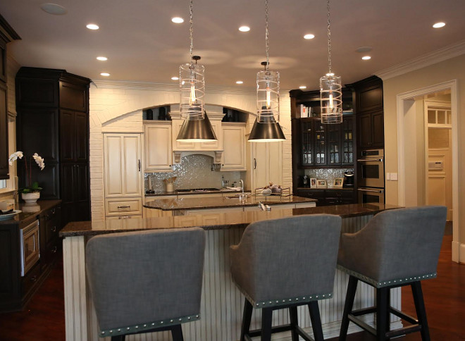 """We did not build this. When we bought it there were pine cabinets, silver backsplash and a lot of orange faux brick. We will eventually remodel it completely but to make it a bit more current on an affordable budget, we chose to stain the pine cabinets a dark ebony. We had the cabinetry built all the way up to the ceiling and added in a lighted display area to make it more current. The backsplash was changed to an ivory Walker Zanger material. No other construction changes were made. Curious to see how this kitchen looked before? See the before picture on the blog Home Bunch"