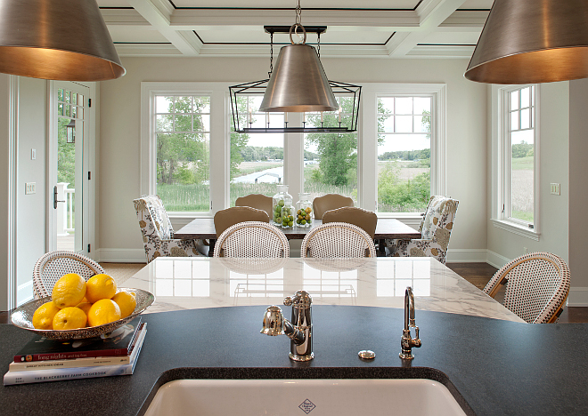 Kitchen nook. Kitchen island opens to kitchen nook. Countertop is Absolute Black Honed Granite.  The dining room features a custom salvaged wood dining table and host chairs in a Kravet fabric. Side chairs are from Cisco. Dining room lighting is Darlana Linear Chandelier from Visual Comfort. #kitchennook #kitchenisland #kitchenlayout Vivid Interior Design. Hendel Homes