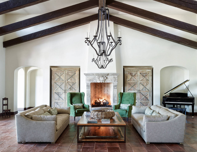 mediterranean-style-living-room-with-terracota-floor-tile-cathedral-ceilings-dark-stained-ceiling-beams-and-wrought-iron-lighting-the-refined-group