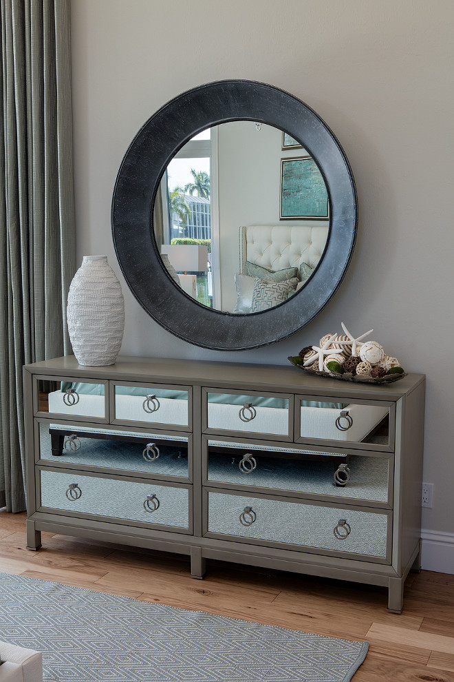 Mirrored Dresser. Bedroom Dresser. Bedroom mirrored dresser. A large round mirror with a wide dark metal frame hangs above a mirrored dresser, which showcases an assortment of coastal accessories such as starfish and seashells. #bedroom #dresser #mirroreddresser