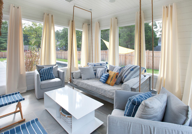 Screened-in porch featuring shiplap siding and ceiling, outdoor swing bed, heated flooring and interchangeable glass and screens, and access to the pool area. #screenedinporch #bedswing #shiplap #shiplapwalls #shiplapceiling Bluewater Home Builders