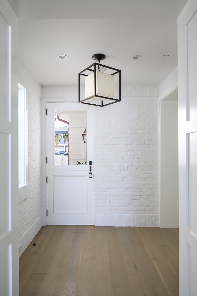 Painted Brick Mudroom. This mudroom, with painted white brick, is located just off the kitchen and features a Dutch door with glass. Lighting is Circa Lighting Caged lantern. Winkle Custom Homes. Melissa Morgan Design. Ryan Garvin Photography