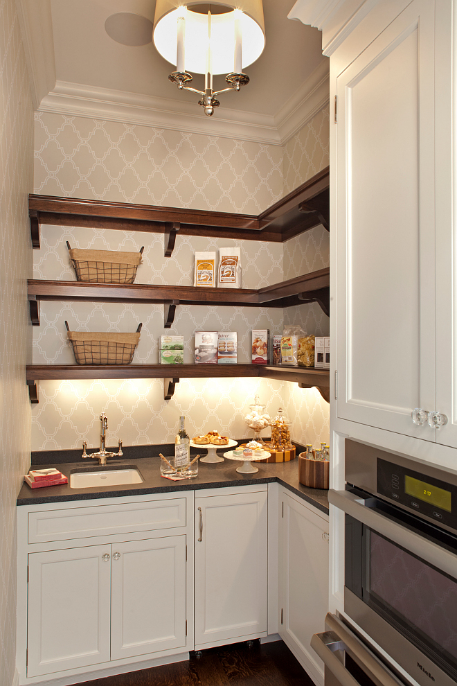 Pantry. Kitchen pantry. Butlers pantry This is a small but very functional pantry. Cabinets are painted in Benjamin Moore Icicle 2142-70. Wallpaper is Thibaut Stanbury Trellis and the open shelves are Cherry wood in a custom stain. #pantry #smallpantry #pantry #butlerspantry Vivid Interior Design. Hendel Homes