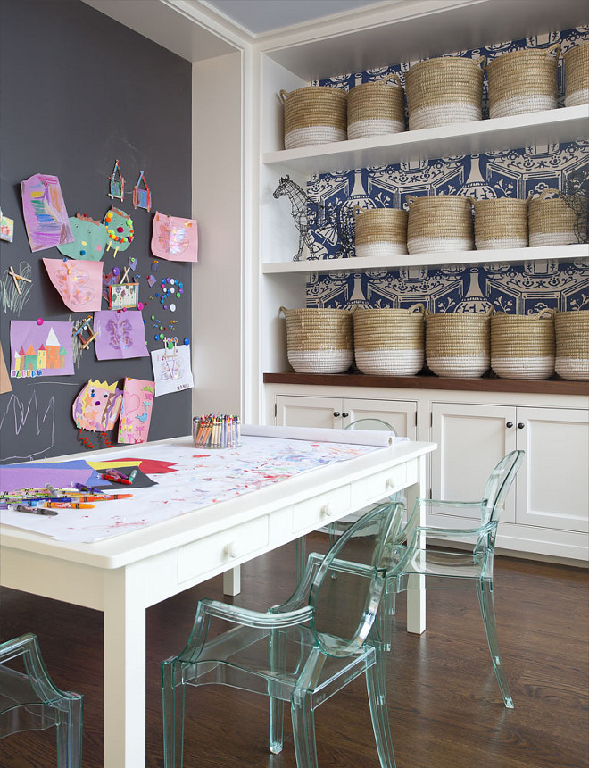 Playroom Chalk Wall. Kids playroom boasts a chalkboard accent wall placed in front of a white play table with drawers lined with Kartell Lou Lou Ghost Chairs in across from alcove clad with white and blue vase wallpaper, David Hicks The Vase Wallpaper, lined with white floating shelves filled with white dipped baskets over built in cabinets topped with wood countertop. #kidsplayroom #playroom #chalk #chalkwall Anik Pearson Architect
