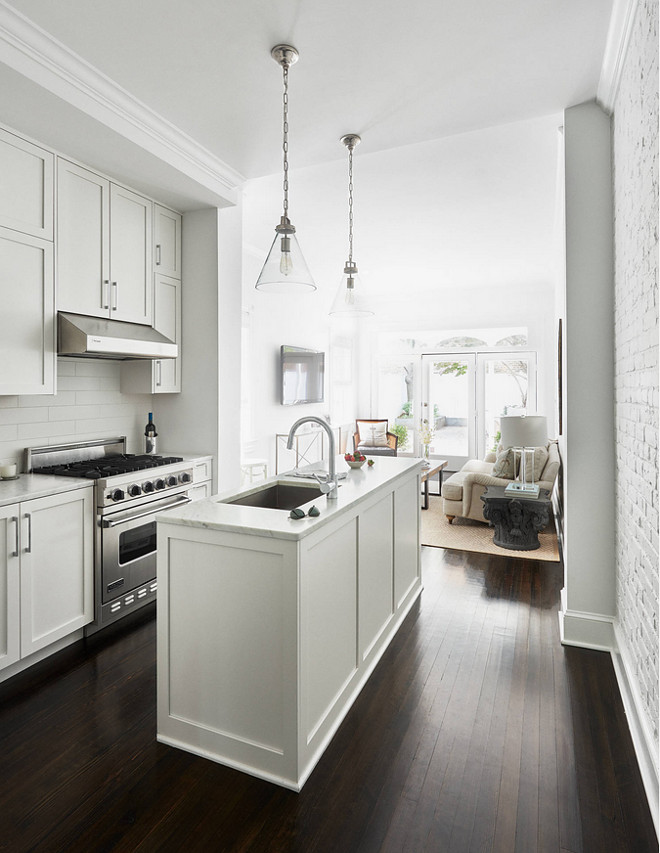 All white small narrow kitchen painted in Benjamin Moore PM-1 Super White. Small white kitchen paint color Benjamin Moore PM-1 Super White #smallkitchen #allwhitekitchen #narrowkitchen #BenjaminMoorePM1SuperWhite Stuart Nordin Designpm-1-benjamin-moore