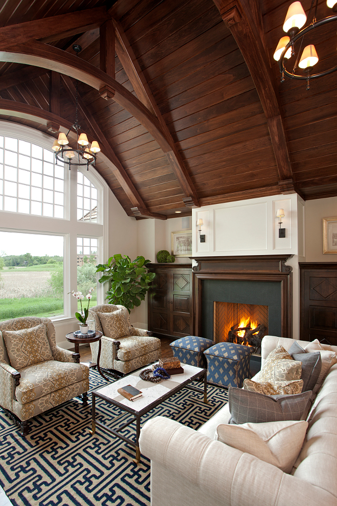 The focal point of this room is the breathtaking ceiling made of Poplar wood. Lighting is the Classic Ring Chandelier from Visual Comfort. Cabinets and mantle are Walnut in custom stain. poplar-tongue-and-groove-ceiling-in-custom-stain #livingroom #ceiling #woodceiling #poplar #ceilings Vivid Interior Design. Hendel Homes