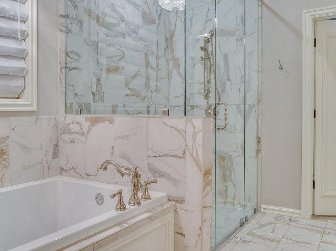 The tub and shower is set in a Calacatta Italian marble, which features gold and gray veins. the-master-bath-is-set-in-a-calacatta-italian-marble-which-features-gold-and-gray-veins Ivy House Interiors