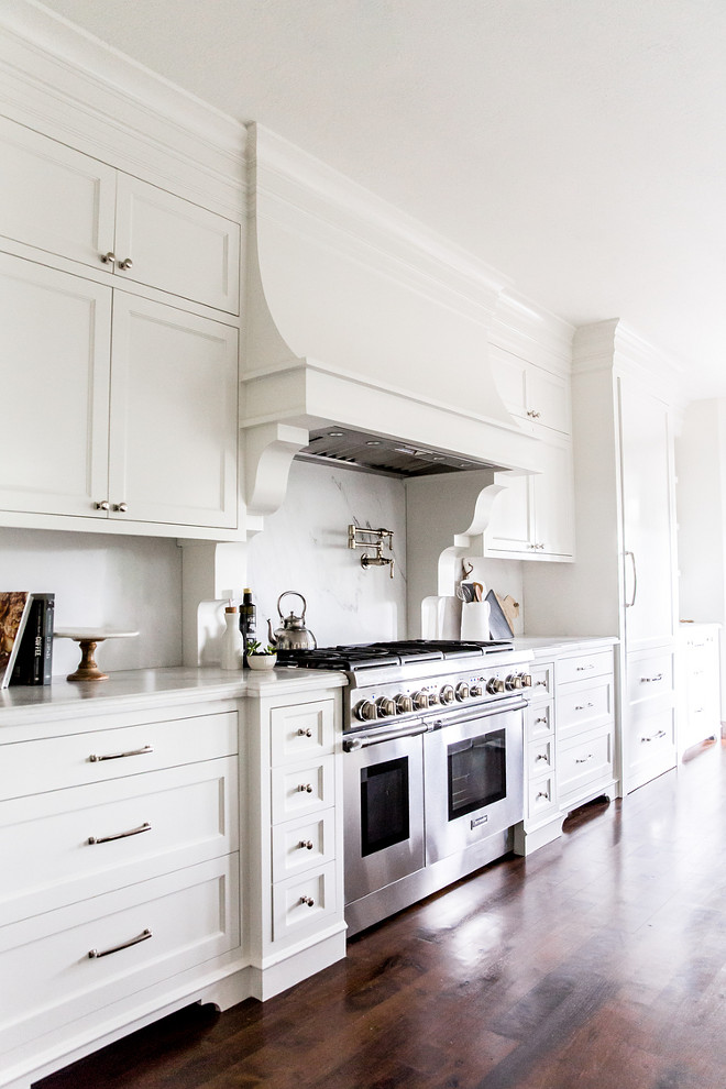 White French Kitchen Hood with Corbels and White Marble Slab Backsplash. White kitchen features white shaker cabinets paired with white marble countertops with gray veining and matching backsplash. A white French kitchen hood with corbels stands over a swing arm pot filler and a stainless steel stove.. white-french-kitchen-hood-with-corbels-and-white-marble-slab-backsplash White French Kitchen Hood with Corbels and White Marble Slab Backsplash #WhiteFrenchKitchen #FrenchHood #Corbels #WhiteMarbleSlab #Backsplash LIV Design Collective.