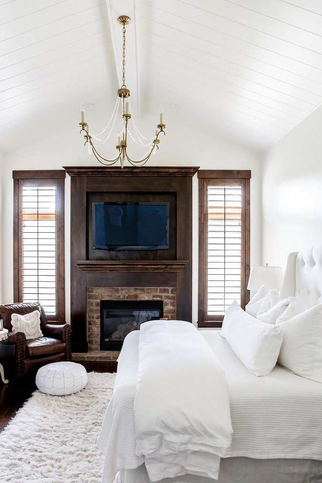 white-bedroom-with-white-shiplap-ceiling-dark-stained-trim-and-exposed-brick-fireplace