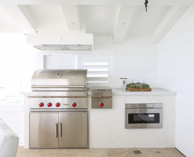 White outdoor kitchen. Grill is by Wolf. Microwave is by Sharp. #outdoorkitchen #grill #wolfgrill Winkle Custom Homes. Melissa Morgan Design. Ryan Garvin Photography