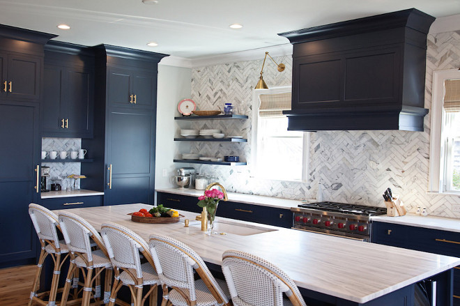 Benjamin Moore Hale Navy Kichen with Brass Accents. This navy kitchen, features an eye-catching navy blue kitchen island is fitted with gray and white quartzite countertops holding an undermount sink with a brass gooseneck facuet and seating five Serena & Lily Riviera Counter Stools. The island faces a wall covered in herringbone marble backsplash tiles holding three floating navy shelves and framing windows covered in bamboo roman shades flanking a navy hood hung over a Wolf range mounted in navy shaker cabinets completed with brass pulls illuminated by brass wing arm sconces. The remaining wall boasts a navy blue paneled double fridge separated by a cafe station and positioned under more navy blue cabinets in Benjamin Moore Hale Navy.benjamin-moore-hale-navy-kichen-with-brass-accents Benjamin Moore Hale Navy Kichen with Brass Accents. #BenjaminMooreHaleNavy #Kichen #Brass Accents Stonington Cabinetry
