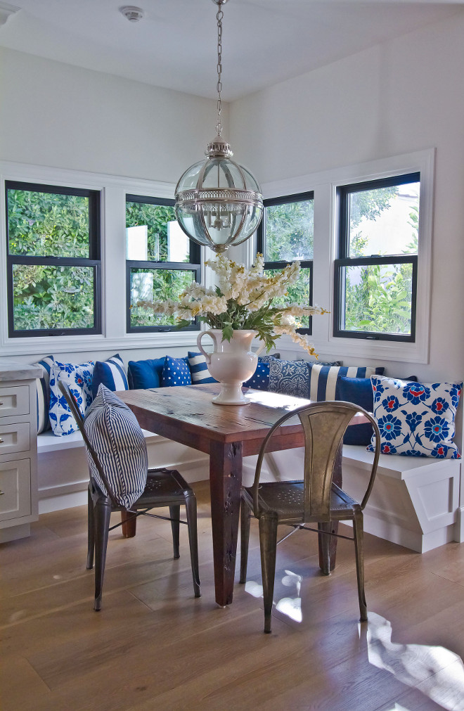 Breakfast room banquette. Breakfast room banquette features an antique farmhouse table, L-shaped banquette, blue and white pillows and black steel windows. The breakfast nook lighting is Restoration Hardware, Victorian Hotel Pendant. #breakfastroom #breakfastroombanquette #banquette #blueandwhite #banquetteideas #lshapedbanquette #lighting #farmhousetable breakfast-room-banquette Home Bunch Beautiful Homes of Instagram Bryan Shap @realbryansharp