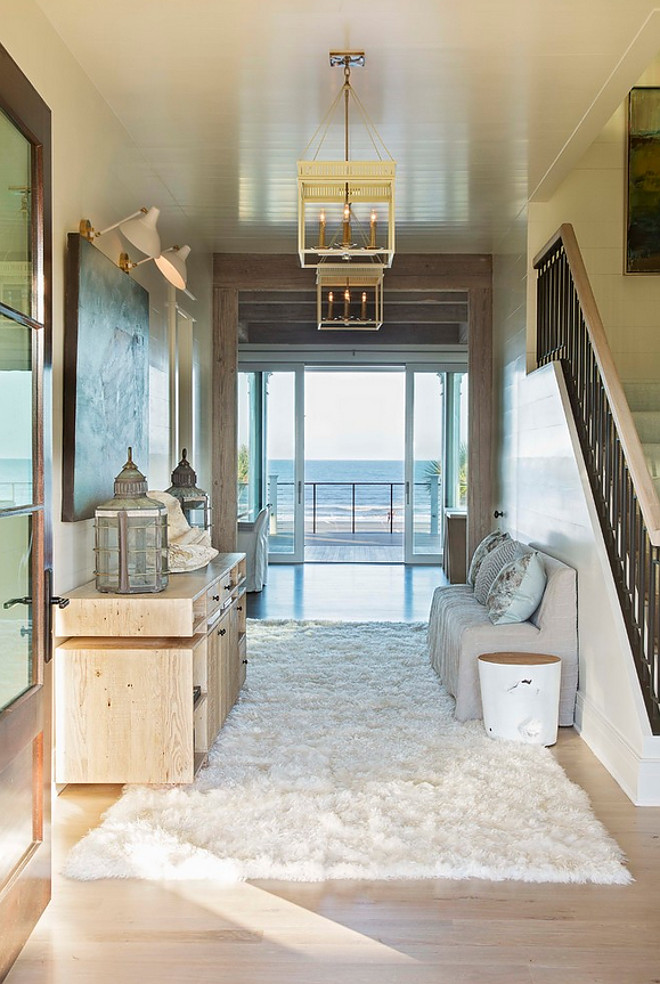 Coastal Foyer. This stunning coastal foyer feature shiplap paneled walls and ceiling with glass doors to an open ocean view. #Foyer #coastalfoyer #shiplap #paneling #shiplapwalls #shiplapceiling Herlong & Associates Architects + Interiors