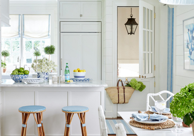 White Kitchen Peninsula with Backless Blue Bistro Stools. Beautifully designed white kitchen with light blue accents boasts Serena & Lily Riviera Backless Stools fitted with light blue cushions placed in front of a white peninsula topped with a white marble countertop while a blue and white is painting mounted on a shiplap wall beside a white glass paneled Dutch door positioned next to an under cabinet white paneled fridge. The fridge is located beside windows covered in white and blue roman shades positioned over an apron sink paired with a polished nickel deck mount gooseneck faucet. White Kitchen Peninsula with Backless Blue Bistro Stools. cottage-kitchen Sarah Bartholomew Design