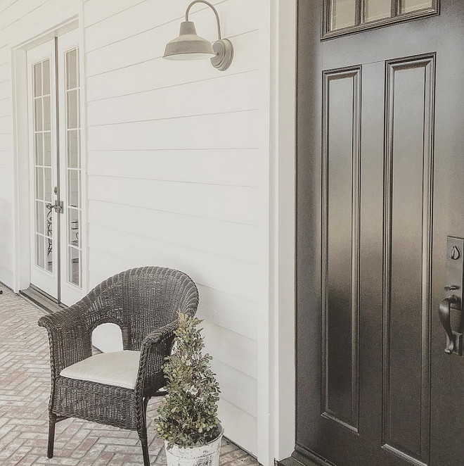The farmhouse porch features white siding painted in Sherwin Williams Pure White, black door painted in Sherwin Williams Tricorn Black and reclaimed brick flooring. farmhouse-front-porch-with-black-front-door-and-reclaimed-brick-flooring #farmhouse #porch #frontporch #paintcolor #SherwinWilliamspurewhite #SherwinWilliamsTricornBlack Home Bunch's Beautiful Homes of Instagram ourfarmhousefit