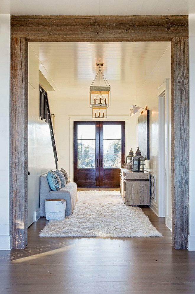 Beamed doorway. A reclaimed beamed doorway opens to main living areas of this beach house. #reclaimedbeams #beameddoorway #doorway #beams #reclaimedbeams Herlong & Associates Architects + Interiors