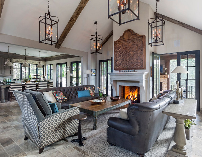 French Country great room. The kitchen opens directly to a great room with cathedral ceiling with reclaimed beams. Lanterns are Bradford Lantern from Troy lighting. Furniture is from Restoration Hardware. Mantel is Cast Limestone #greatroom #FrenchCountry #beams Hendel Homes