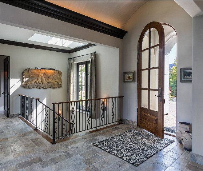 French foyer. The foyer features arched barrel ceiling, custom stairway railings and a skylight. Floor tile is Italian Limestone. #FrechFoyer #Foyer #BarrelCeiling #Limestonefloortile #limestone french-foyer Hendel Homes