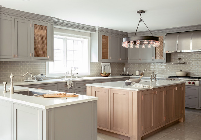 Grey kitchen. Grey kitchen features gray shaker cabinets paired with white quartz countertops and a gray brick tile backsplash. A kitchen peninsula is fitted with a stainless steel sink and satin nickel hook and spout faucet. A secondary kitchen sink stands across from the island and under a window flanked by mesh metal cabinets. A Ralph Lauren Roark Modular Chandelier illuminates a honey colored kitchen island fitted with a prep sink. A stainless steel barrel kitchen hood stands over a swing arm pot filler and an integrated Wolf cooktop accented with pot and pan drawers below. #Greykitchen #shakercabinets #kitchen grey-kitchen RC Studio