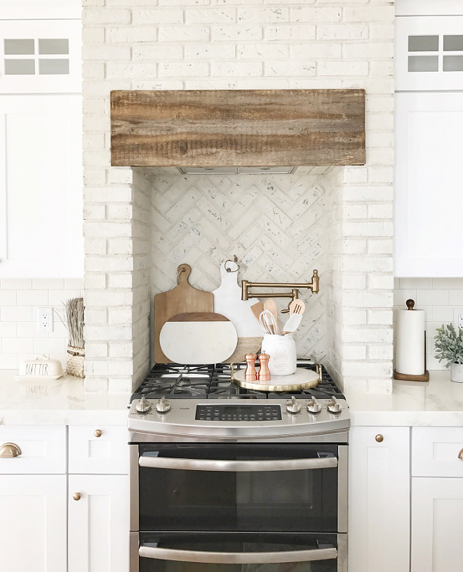 Kitchen brick hood and kitchen brick backsplash. Using distressed painted brick in kitchens is a trend that is here to stay. I love that Nina chose to use the painted brick in a herringbone pattern behind the stove. #kitchenbrick #brickhood #brickbacksplash #distressedpaintedbrick #paintedbrick #whitebrick #brick #herringbonebrick #farmhousekitchen Beautiful Homes of Instagram @nc_homedesign via Home Bunch