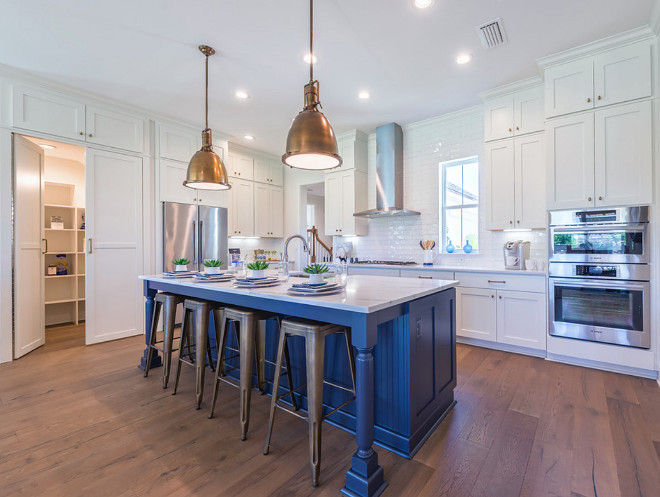 Kitchen with hidden walk-in pantry.. White kitchen with blue and island hidden walk in pantry cabinet. #Kitchen #hiddenpantry #walkinpantry #kitchenpantry kitchen-with-hidden-walk-in-pantry Cottage Home Company