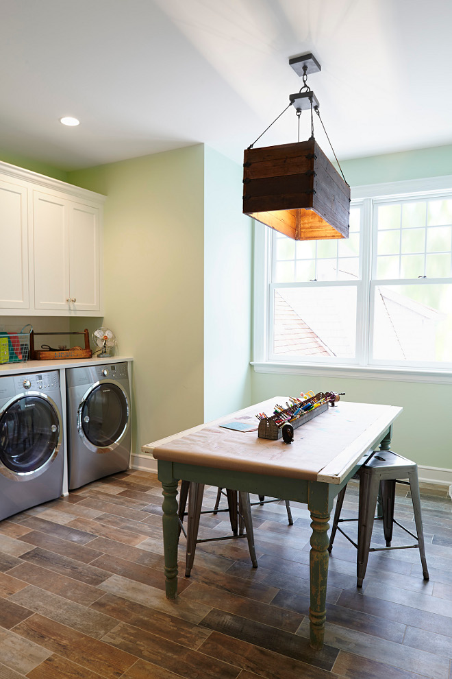 Benjamin Moore 2029-40 Stem Green. Laundry room and Craft room. This is such a functional space. Paint color is Benjamin Moore 2029-40 Stem Green. Lighting is from Currey and Co. Combination of laundry room and craft room. Benjamin Moore 2029-40 Stem Green #BenjaminMooreStemGreen #Laundryroom #Craftroom #interiors laundry-room-craft-room Hendel Homes