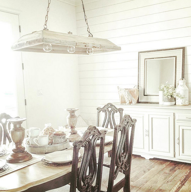Farmhouse dining room. The farmhouse dining room features an old cabinet, painted in a soft gray by the homeowners, and shiplap walls. The rustic dining room chandelier is from Painted Fox. rustic-farmhouse-dining-room-with-shiplap-walls #farmhouse #Farmhousediningroom #diningroom #shiplap #rustic Home Bunch's Beautiful Homes of Instagram ourfarmhousefit