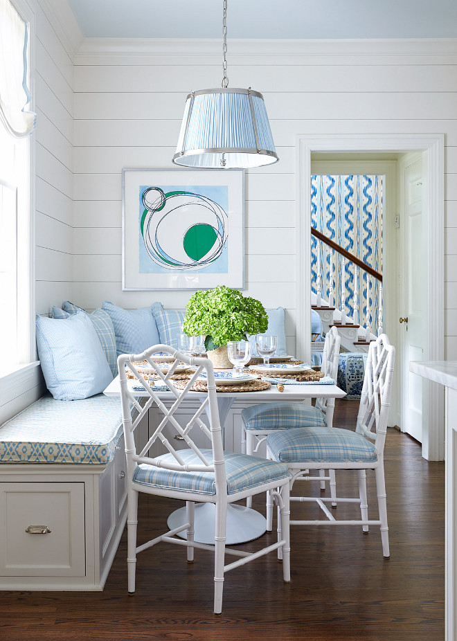 Shiplap White and Blue Breakfast Room with White Bamboo Chairs. Blue and white breakfast room features a blue Vaughn Nickel Hanging Shade Pendant hung from a blue ceiling over a square white dining table seating three white bamboo chairs accented with blue plaid seat cushions complementing blue plaid and solid blue pillows placed atop an L-shaped dining bench adorning polished nickel cup pulls and a blue trellis cushion positioned beneath a window dressed in a white roman shade. The space is completed with a blue and white print mounted above the bench on a shiplap wall. shiplap #Shiplap #WhiteandBlue #BreakfastRoom #WhiteBambooChairs Sarah Bartholomew Design