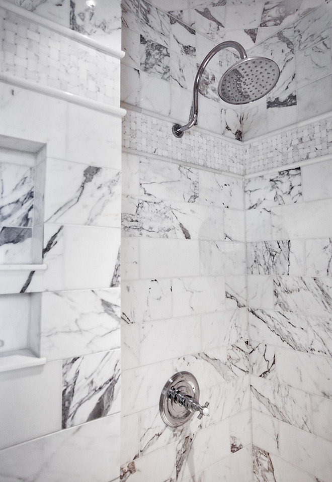 Shower fixtures. A view of this custom shower made from a design mixture of large marble subway tiles, small basket weave, and upper square tiles. Chrome rainhead shower with trim and built-in niche. shower #showerfixture Karr Bick Kitchen and Bath