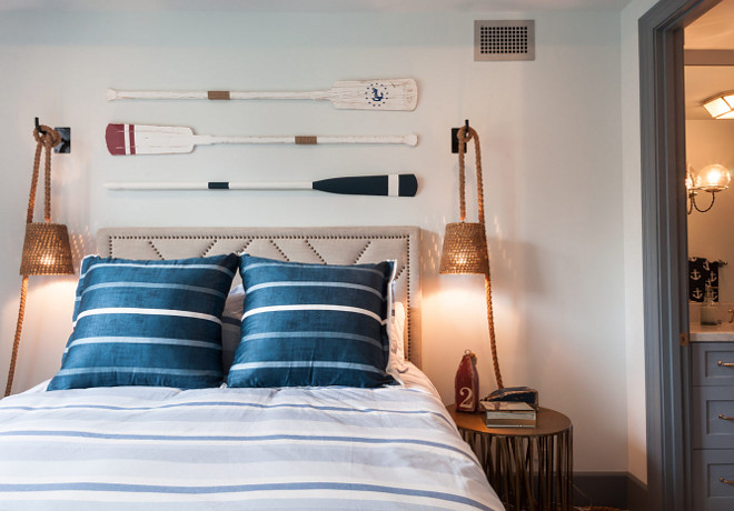 Vintage Oars Over Beige Nailhead Headboard. Cottage bedroom features vintage decorative wall oars fixed between woven swing arm rope sconces over a beige nailhead headboard accenting a bed dressed in a blue and white striped duvet topped with blue striped pillows flanked by gold nightstands. #VintageOars #NailheadHeadboard Matt Morris Development