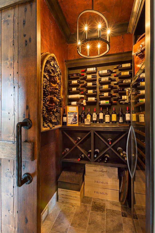 Wine cellar walls are paneled in Alder wood with a dark stain. The wine cellar lighting is Colwyn Chandelier from Currey and Co. Wine cellar paneleds walls. #Winecellar #walls #paneling #Alder #wood #darkstain wine-cellar Hendel Homes