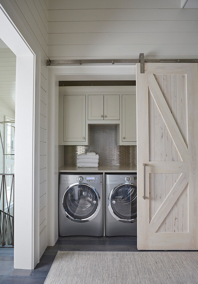 Barn door closet laundry room. Closet Laundry Room with Pecky Cypress Barn Door on Rails. A pecky cypress barn door on rails opens to a hallway laundry room filled with light gray shaker cabinets suspended over a stainless steel mini brick tile backsplash and an enclosed washer and dryer. Washer and dryer are Electrolux. barn-door-closet-laundry-room #barndoor #closetlaundryroom #laundryroom #closet #barndoorideas #closetbarndoor