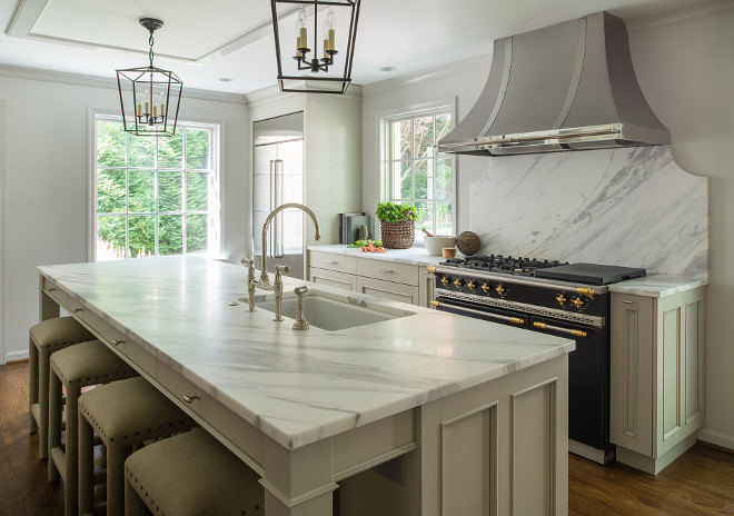 Classic Kitchen Design. Classic Kitchen Design with soft gray cabinets, large kitchen island with white and gray honed marble countertop, tow pairs of Darlana pendants. This classic kitchen design also features a stainless custom hood and marble slab backsplash. #ClassicKitchenDesign ClassicKitchen #kitchen #kitchenDesign Anthony Wilder. John Cole Photography.