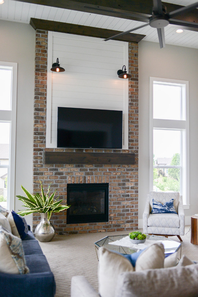 Farmhouse Fireplace. This farmhouse-inspired fireplace features brick, shiplap and barn lighting. #FarmhouseFireplace #Farmhouse #Fireplace #brick #shiplap #barnlighting #barnlight Millhaven Homes