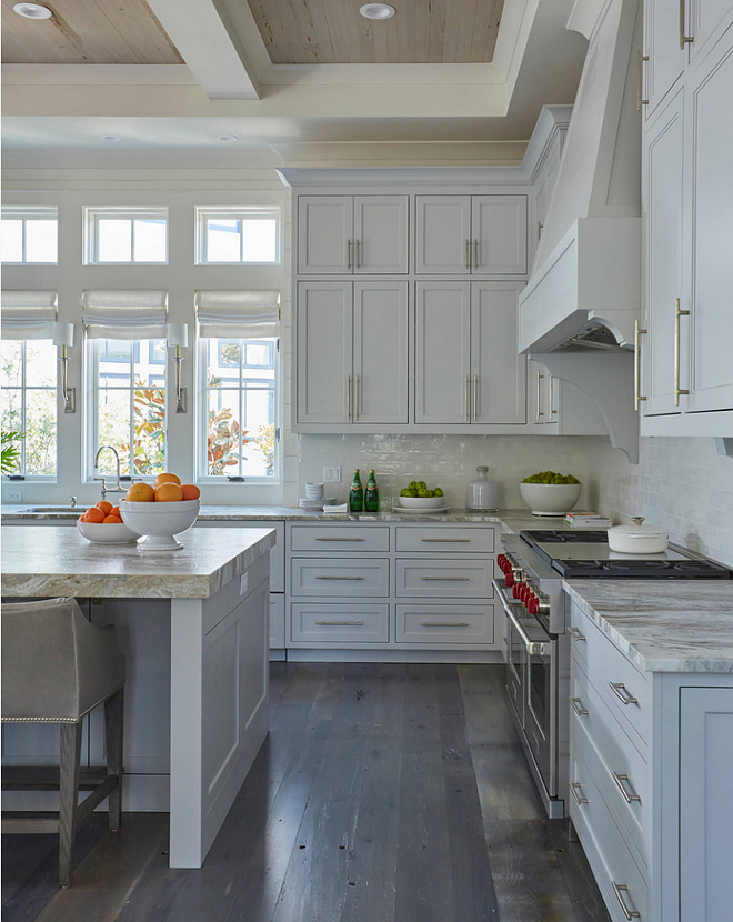 Stacked Kitchen Cabinets with Rustic Wood Floors. Stacked Kitchen Cabinets with Rustic Wood Floors. The kitchen features light gray stacked cabinets adorned with long satin nickel pulls paired with quartzite countertops and a light gray glazed tiled backsplash. The rustic wood floors are custom dark stained. #rusticflooring #rusticwoodfloors #StackedKitchenCabinets #RusticWoodFloors #rusticwood #rusticplankfloor grey-brown-hardwood-floor Geoff Chick & Associates