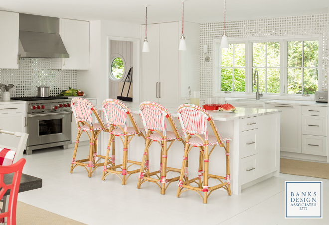 White kitchen with pops of color. White kitchn pops of color ideas. Red, the homeowner's favorite color, is brought to the kitchen through the rattan French bistro barstools and pendants. Red pendants are Rejuvenation McCoy, brushed nickel.  Floors are existing, painted Benjamin Moore Decorator White. #whitekitchen #color  Banks Design Associates, LTD & Simply Home