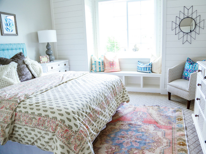 This guest bedroom is lovely with its pop of bright colors and shiplap window-seat. Millhaven Homes