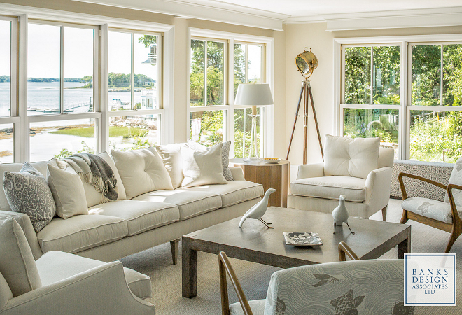 With floor-to-ceiling windows, the living room truly takes advantage of the stunning waterviews. The interior designer, Linda Banks, used clear glass lamps to not obscure the view and keep an airy feel. The sofa and chairs are covered in an indoor/outdoor canvaslike fabric. All furnishings in this home were sourced through Simply Home. Lighting: Currey & Company Glasshouse Table Lamp, white. Lamps flanking sofa: medium Trumpet Lamp by Barbara Cosgrove. Banks Design Associates, LTD & Simply Home