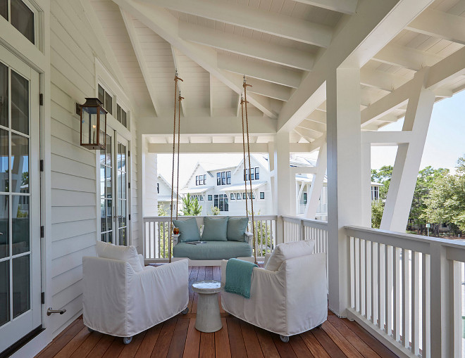 Porch Swing. White and turquoise porch swing. Beach Home Porch with Rope Swing. Beach home porch features a rope swing sofa adorned with blue cushions facing a pair of white slipcovered chairs. #porch #porchswing #ropeswing Geoff Chick & Associates porch-swing-white-and-turquoise-porch-swing