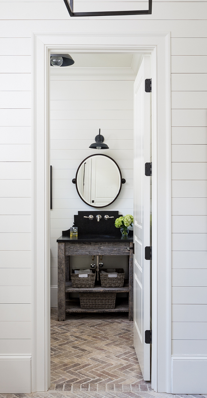 Farmhouse powder room. The designer decided to keep this powder room informal because of its close proximity to the pool. They used weathered wood for the console and leathered black pearl granite for the countertop and backsplash. Light fixture is RH. The brick in the herringbone pattern adds interest to the floor. #farmhouse #powderroom #farmhouseinteriors #shiplap Interiors by Courtney Dickey. Architecture by T.S. Adam Studio.