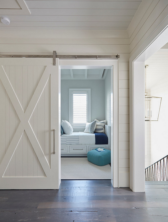 Shiplap and barn door. This white shiplap barn door opens to reveal a kids' bedroom filled with white built-in beds with storage drawers. #whitebarndoor #shiplapbarndoor Hall features shiplap and bedrooms with barn door. #barndoor #shiplap shiplap-and-barn-door