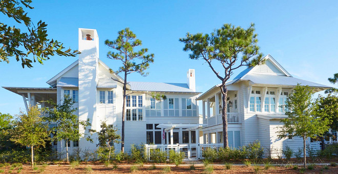 Designed by Geoff Chick & Associates and built by Chris Clark Construction Incorporated, this Florida beach house is full of new coastal design ideas! The architectural details are truly inspiring. Walls are paneled with white shiplap and the ceilings, when not featuring shiplap, are beautifully crafted with coffered trim and pecky cypress wood. Located in 30A, this beach house has a very soothing, relaxing color palette that easily transports you to a sunny summery day. #Beachhouse #beachhouseexterior white-beach-house-exterior Geoff Chick & Associates