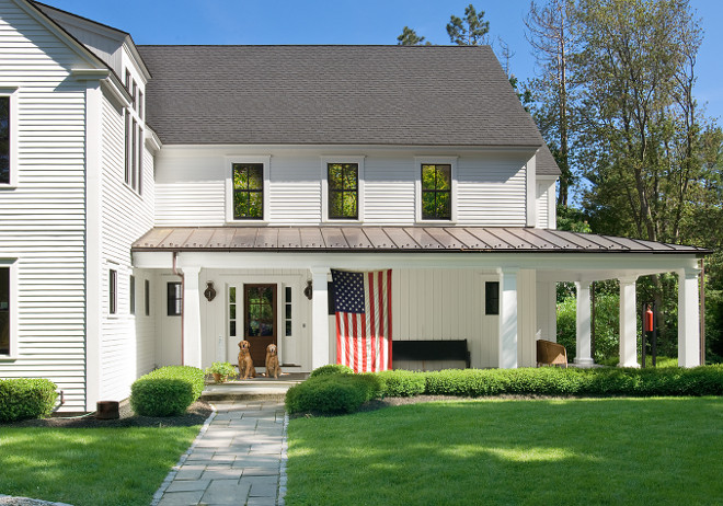 White Farmhouse. White Farmhouse with American Flag on Porch. White Farmhouse. #WhiteFarmhouse #AmericanFlag #Porch #frontporch White Farmhouse white-farmhouse Banks Design Associates, LTD & Simply Home