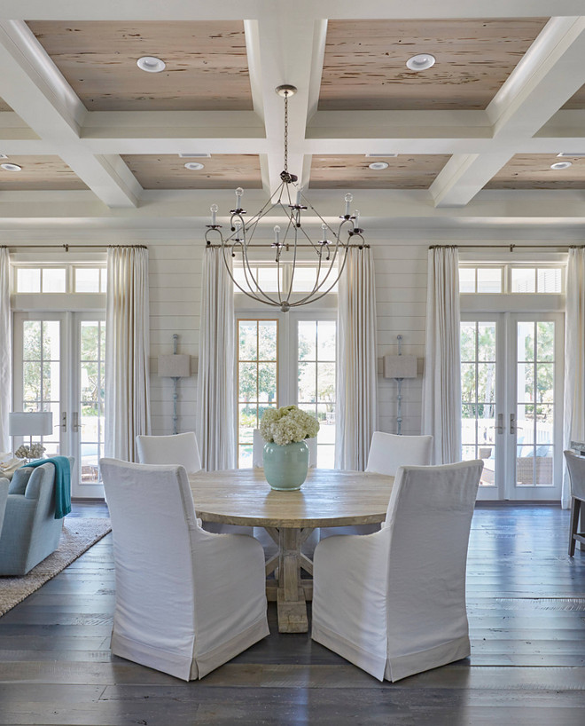 Dining Room Coffered Ceiling with Pecky Cypress Trim. The dining room boasts a glossy white coffered ceiling accented with pecky cypress coffers accented with an iron chandelier. The round salvaged wood dining table surrounded by white slipcovered dining chairs. Lighting is Lowcountry Originals Spring Island Basket. #lowcountryoriginals #lighting #springislandbasket #chandelier #DiningRoom #CofferedCeiling #PeckyCypress #Trim