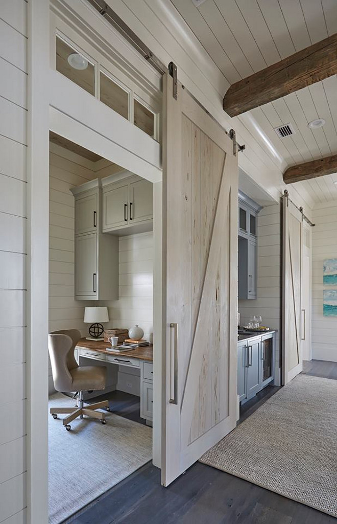 Whitewashed Barn Door. Whitewashed Barn Door Ideas. Office with Pecky Cypress Whitewashed Barn Door. A pecky cypress barn door opens to reveal a home office with light gray cabinets suspended over a gray built-in desk with wood top. Barn doors are painted in a custom whitewash stain. whitewash-barn-door #WhitewashedBarnDoor