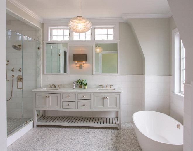 The master bathroom features carrara marble countertop, subway tile half wall wainscotting and marble mosaic floor tile. Bathroom half wall tile wainscotting and open vanity. Bathroom features Bathroom half wall tile wainscotting and open vanity painted in a soft gray paint color. Bathroom half wall tile wainscotting. #Bathroom #halfwalltilewainscotting #halfwalltile #wainscotting #halfwallwainscotting #walltilewainscotting #walltile #openvanity #softgray #paintcolor Main Street Kitchens at Botellos